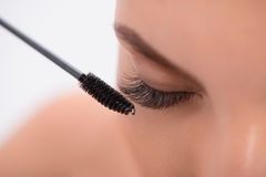 Pretty girl with extended lashes doing make-up Stock Images