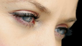 Pretty girl with eyeliner blinking close up stock video
