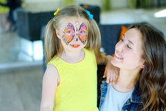 Pretty girl with face painting of a butterfly with babysitter Stock Photo