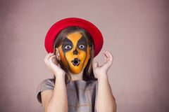 Pretty girl with face painting of a pumpkin Royalty Free Stock Photography