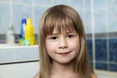 Pretty girl face portrait, smiling child with beautiful eyes and long wet fair hair on blurred background of bathroom stock photo