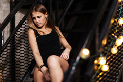 Pretty girl with fair hair wearing black outfit posing sitting on steps of metal fire escape staircase Royalty Free Stock Images