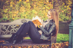 Pretty girl in fall reading Stock Image
