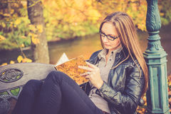 Pretty girl in fall reading Royalty Free Stock Photos