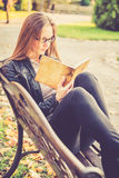 Pretty girl in fall reading Stock Images
