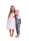 Little brother and sister isolated on a white background. Cute boy and girl standing together. Family concept. stock photography