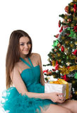 Pretty girl in fancy dress under Christmas tree Stock Image