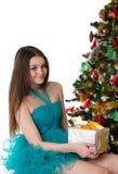 Pretty girl in fancy dress under Christmas tree stock image