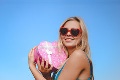 Pretty girl in fancy sunglasses holding pink heart Stock Photo