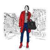 Pretty girl in fashionable clothes in the streets with a red coat. Stock Image