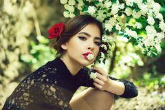 Pretty girl with fashionable spanish makeup, rose flower in hair. Pretty girl with fashionable makeup and red lips, has rose flower in hair hispanic or spanish stock images