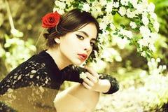 Pretty girl with fashionable spanish makeup, rose flower in hair. Spanish girl. pretty girl with fashionable makeup and red lips, has rose flower in hair stock photos