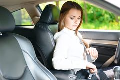 Pretty girl fastening seat belt in car Stock Image