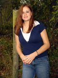 Pretty girl and fence post. Pretty young woman leaning on a fence post stock photo