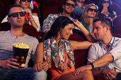 Pretty girl flirting in cinema. Young couple sitting in movie theater, girl flirting with boy on next seat Royalty Free Stock Image