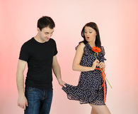 Pretty girl and flirting man with a flower Stock Images