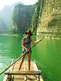 Pretty girl floating on a bamboo raft Stock Photo