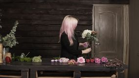 A pretty girl florist on a dark background makes a composition of flowers. Modern, wooden interior.  stock footage