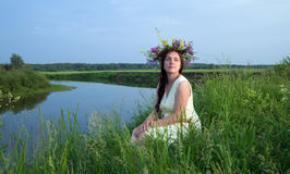 Pretty girl  in flower chaplet against river Royalty Free Stock Photography