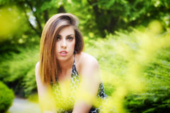 Pretty girl among flowers and green plants Royalty Free Stock Photos