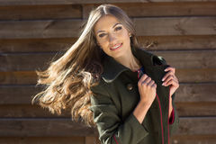 Pretty girl with flying hair near wooden wall Stock Images