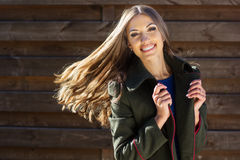 Pretty girl with flying hair near wooden wall Royalty Free Stock Photo