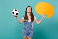 Pretty girl football fan cheer up support team with soccer ball empty blank yellow Say cloud speech bubble blowing air. Kiss isolated on blue turquoise stock photos