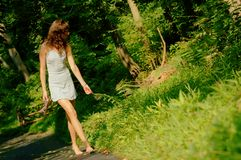 Pretty girl on forest path. Pretty girl on forested pathway royalty free stock photos