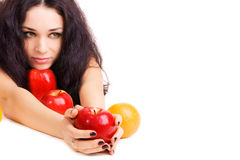 Pretty girl with fresh red apples and orange Royalty Free Stock Photography