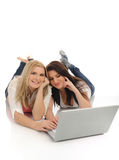 Pretty girl friends in internet on laptop computer Stock Photos