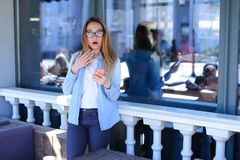 Female person standing at street cafe and using smartphone with fright emotion. Pretty girl with fright emotion using smartphone in pink case and standing at royalty free stock photo