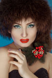 Pretty girl in a fur hat and a Christmas tree in the neck Stock Photography