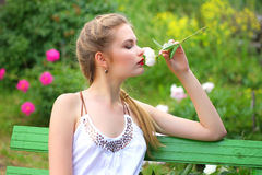 A pretty girl in the garden on a bench with a white flower in hi Royalty Free Stock Image