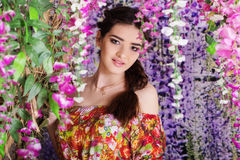 Pretty girl in garden with magic wistaria flowers Stock Image