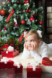 Pretty girl with gift dreaming near christmas tree Stock Photo