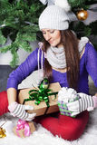 Pretty girl with gifts beside green Christmas Tree Royalty Free Stock Image