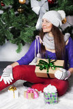 Pretty girl with gifts beside green Christmas Tree Stock Photos