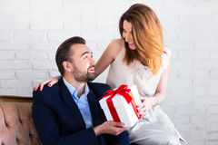 Pretty girl giving gift box to her boyfriend Stock Photos