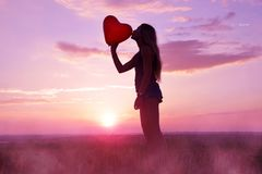 Pretty girl giving a kiss red balloon in the shape heart. Pretty girl giving a kiss red balloon in the shape heart at sunset stock photos