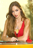 Pretty girl with glass of champagne. Beautiful pretty woman in red dress on a sofa with glass of champagne royalty free stock image