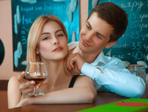 Pretty girl with glass of wine and hugs her boyfriend from behin Royalty Free Stock Photography
