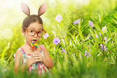 Pretty girl with glasses dressed in easter bunny ears holding lo Royalty Free Stock Images