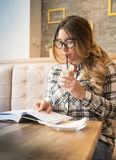Pretty girl with glasses drinking strawberry bannana smoothie an. Pretty girl drinking strawberry bannana smoothie and reading her interesting book at cafe Royalty Free Stock Photo