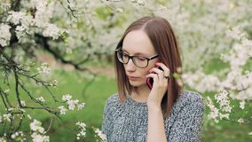 Sad girl in glasses speaking on cellphone in the blooming garden. stock footage