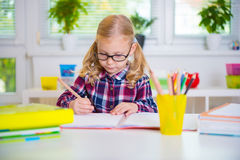 Pretty girl in glasses learns at school. Pretty diligent girl in glasses learns at school Royalty Free Stock Images