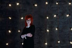 Pretty girl in glasses poses near wall. In black studio with garlands of lamps Stock Photography
