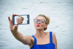 Pretty girl in glasses sending air kiss and making. Portrait of pretty girl making selfie with smartphone. Young woman wearing big glasses sending air kiss on Stock Photos