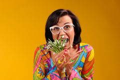 Pretty girl in glasses and snowdrops. In the hands over yellow background Royalty Free Stock Image