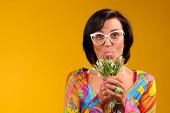 Pretty girl in glasses and snowdrops. In the hands over yellow background Royalty Free Stock Photos