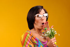 Pretty girl in glasses and snowdrops. In the hands over yellow background Stock Photography
